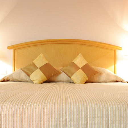 Bed in a hotel room at night Stock Photo