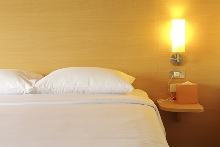 accommodation: Bed in a hotel room at night Stock Photo