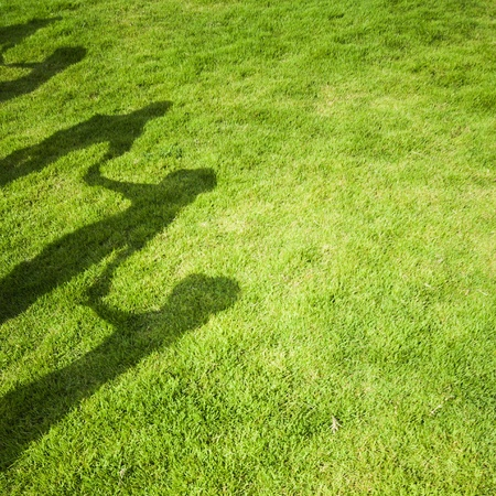 Group people shadow on green grass photo