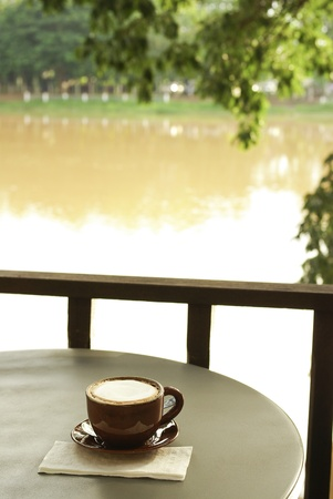 afternoon break: Coffee cup at riverside view Stock Photo