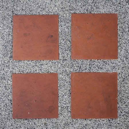 Pebbles stone road texture background with square orange tile photo