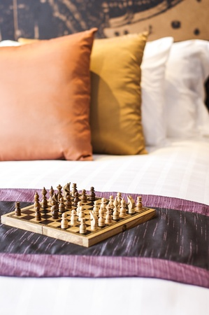 boutiques: Chess on bed in hotel room Stock Photo