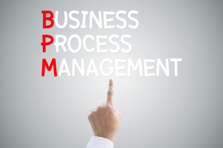 Business process management hand press concept on grey background photo
