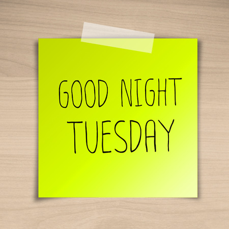 Good night tuesday sticky paper on brown wood background texture photo