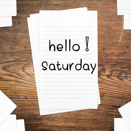 saturday: Hello Saturday on paper and wood table desk Stock Photo