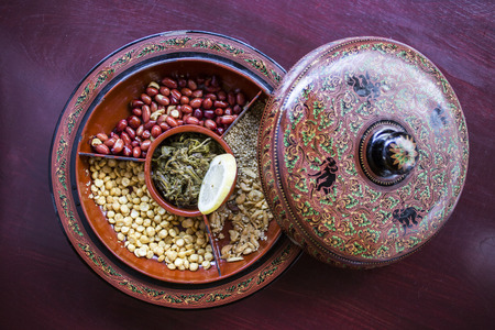 A selection of typical Myanmar snacks: tasty and spicy seeds, nuts and pickled tea leaves. Archivio Fotografico
