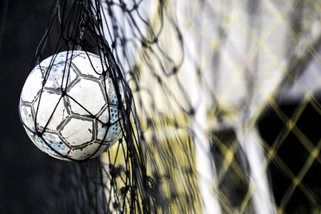 revel: A soccer ball stuck on the net behind goal
