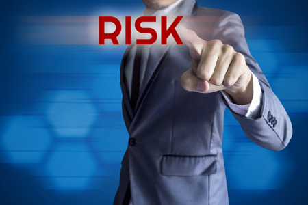 Business man touch modern interface for Risk concept on blue background. photo