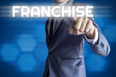 franchise: Business man touch modern interface for Franchise concept on blue background. Stock Photo