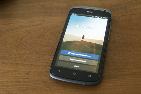 htc: THAILAND - SEPTEMBER 05, 2014: Instagram login screen application on htc smartphone with wood background