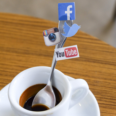 printed media: CHIANG MAI, THAILAND - SEPTEMBER 24, 2014: Social media brands printed on sticker and placed on coffee spoon wood table. Include Facebook, Twitter, Instagram and Youtube. Editorial