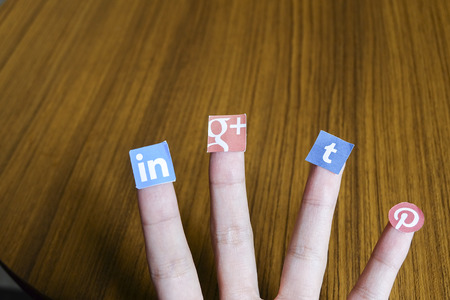 CHIANG MAI, THAILAND - SEPTEMBER 24, 2014: Social media brands printed on sticker and placed on human finger. Include Google plus, Linkedin, Tumblr and Pinterest.