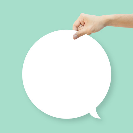 talk balloon: Hand hold white bubble quote chat on green background Stock Photo