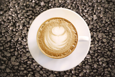 Hot Cappuccino with white cup on coffee beans photo