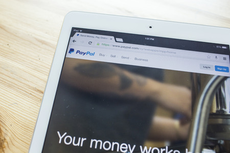 THAILAND - SEPTEMBER 07, 2014: Paypal website displayed on tablet screen against wood background. Established in 1999, PayPal allows payments and money transfers to be made through the Internet.
