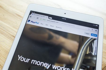 CHIANG MAI, THAILAND - SEPTEMBER 07, 2014: Paypal internet page on screen of ipad Air. PayPal is a popular and international method of money transfer via the Internet.