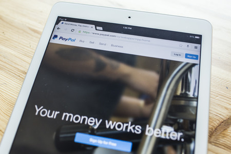 paypal: CHIANG MAI, THAILAND - SEPTEMBER 07, 2014: Paypal internet page on screen of ipad Air. PayPal is a popular and international method of money transfer via the Internet.