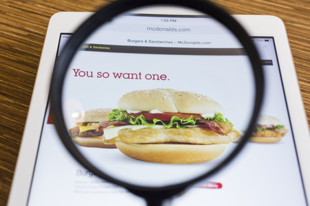 CHIANG MAI, THAILAND - SEPTEMBER 17, 2014: Close up of McDonalds homepage on Apple iPad Air through a magnifying glass on wood table.