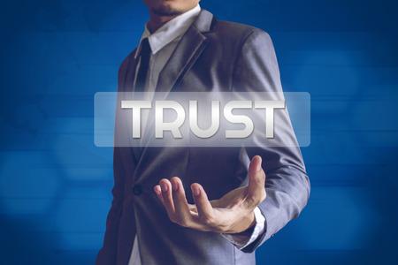 positiveness: Businessman or Salaryman with Trust text modern interface concept. Stock Photo