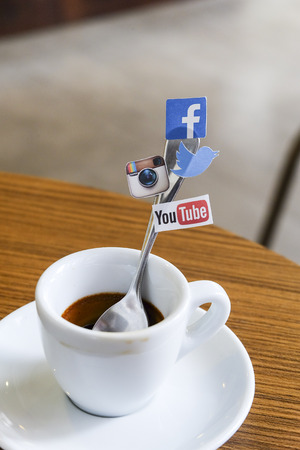 CHIANG MAI, THAILAND - SEPTEMBER 24, 2014: Social media brands printed on sticker and placed on coffee spoon wood table. Include Facebook, Twitter, Instagram and Youtube. Editorial
