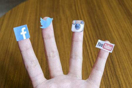 CHIANG MAI, THAILAND - SEPTEMBER 24, 2014: Social media brands printed on sticker and placed on human finger. Include Facebook, Twitter, Instagram and Youtube. Publikacyjne