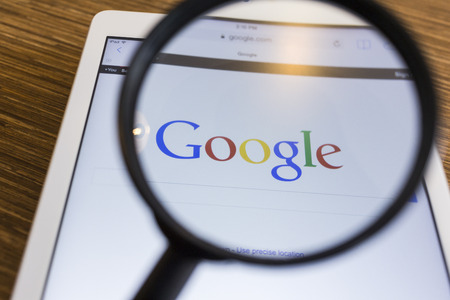 search engines: CHIANG MAI, THAILAND - SEPTEMBER 17, 2014: Magnifying glass of Google search page view on web browser Apple iPad Air device. Editorial