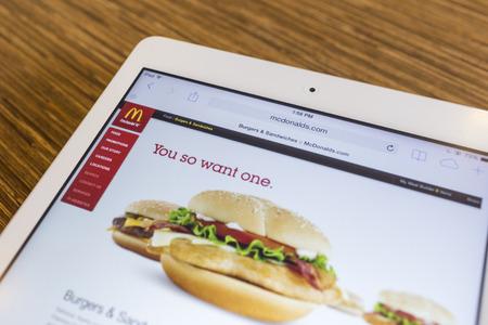 tiendas de comida: CHIANG MAI, Tailandia - el 17 de septiembre 2014: Cierre de la página principal de McDonald en el iPad de Apple de aire a través de una lupa en la mesa de madera.