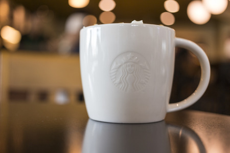 CHIANG MAI, THAILAND - OCTOBER 02, 2014: Starbucks coffee caramel latte white mug in Starbucks Cafe Chiang Mai Thailand. Starbucks is the largest coffeehouse company in the world. Editorial