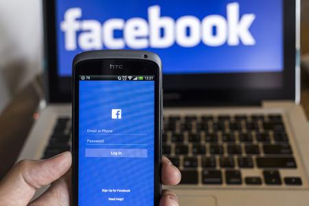 CHIANG MAI, THAILAND - 21 oktober 2014: Facebook applicatie inlogpagina op smartphone en Facebook-logo op de achtergrond. Facebook is het grootste en meest populaire social networking site in de wereld.