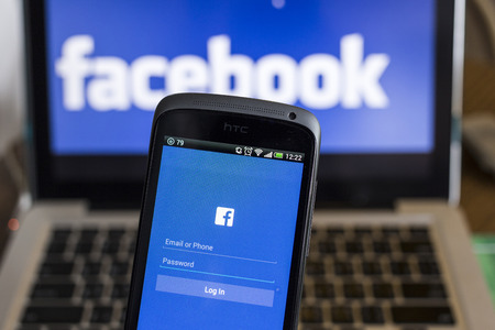 htc: CHIANG MAI, THAILAND - OCTOBER 21, 2014: Facebook application sign in page on smartphone and facebook logo on background. Facebook is largest and most popular social networking site in the world.