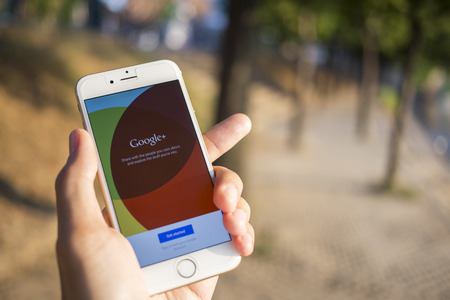 plus: CHIANG MAI, THAILAND - JANUARY 04, 2015: Man hold Apple iphone 6 with Google+ social network of the Google company. Information of a social network, influences Google search results. Editorial