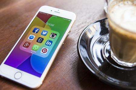 redes de mercadeo: CHIANG MAI, Tailandia - el 22 de abril 2015: Todos los iconos de medios sociales populares en la pantalla del dispositivo smartphone de Apple iPhone 6 en la mesa de café.