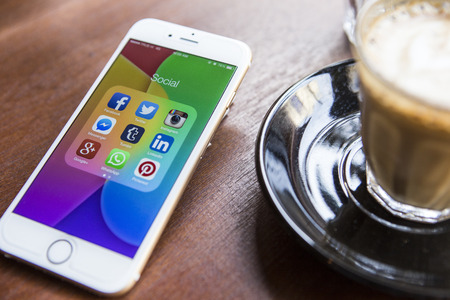 Media: CHIANG MAI, THAILAND - APRIL 22, 2015: All of popular social media icons on smartphone device screen Apple iPhone 6 on coffee table.