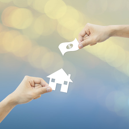 hand hold: Business concept Hand hold white paper house and money bokeh background. Stock Photo