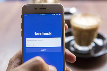 Chiang Mai, Thailand - 22. April 2015: Ein Mann, der versucht, in Facebook-Anwendung mit Apple iPhone 6. Facebook ausloggen ist größte und beliebteste soziale Netzwerk der Welt. Standard-Bild - 42011780