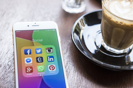 CHIANG MAI, THAILAND - APRIL 22, 2015: All of popular social media icons on smartphone device screen Apple iPhone 6 on coffee table.