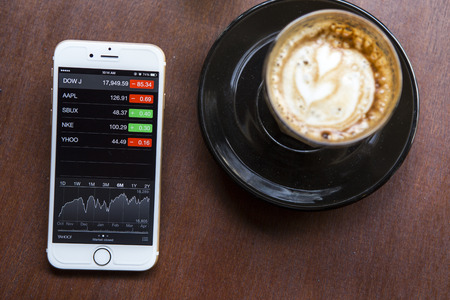 buy shares: CHIANG MAI, THAILAND - APRIL 22, 2015: iPhone 6 with application Stocks of Apple on the screen in coffee shop cafe. iPhone 6 was created and developed by the Apple inc.