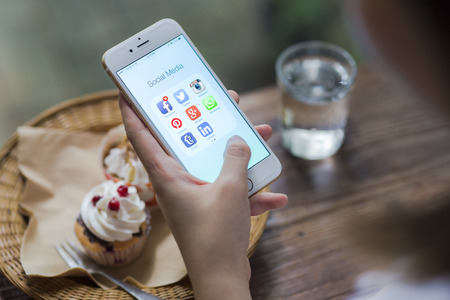 coffee and cake: CHIANG MAI, THAILAND - JUNE 28, 2015: All of popular social media icons on smartphone device screen Apple iPhone 6 on woman hand in coffee shop cafe. Editorial