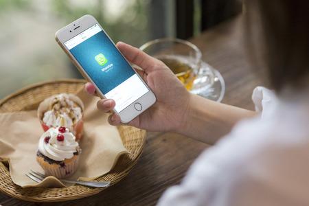 CHIANG MAI, THAILAND - 28 juni 2015: De vrouw houdt iPhone 6 met sociale internet service WhatsApp op het scherm in de coffeeshop. iPhone 6 werd gecreëerd en ontwikkeld door Apple inc. Redactioneel