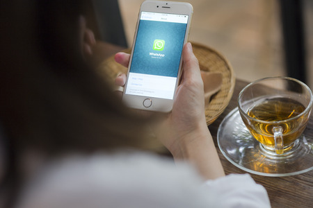 CHIANG MAI, THAILAND - JUNE 28, 2015: Woman hold iPhone 6 with social Internet service WhatsApp on the screen in coffee shop. iPhone 6 was created and developed by the Apple inc. Editorial
