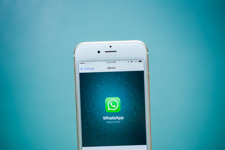 CHIANG MAI, THAILAND - 2 september 2015: iPhone 6 met sociale internet service WhatsApp scherm op een blauwe achtergrond. iPhone 6 werd gecreëerd en ontwikkeld door Apple inc.