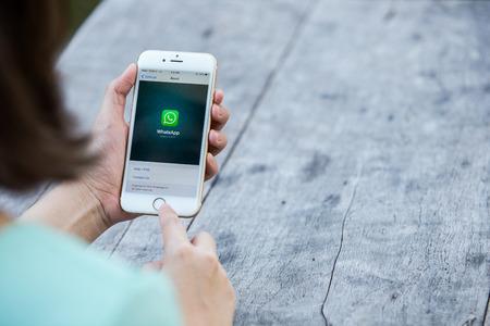 CHIANG RAI, THAILAND - 13 september 2015: De vrouw probeert om de sociale internet service WhatsApp scherm te gebruiken op een blauwe achtergrond. iPhone 6 werd gecreëerd en ontwikkeld door Apple inc. Redactioneel