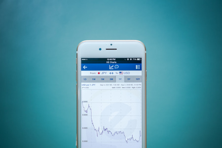 stockbroker: CHIANG MAI, THAILAND - SEPTEMBER 02, 2015: Smart phone running a exchange rate app with charts and data.