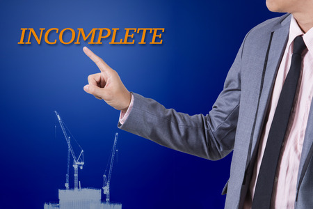 incomplete: Businessman touch incomplete word on business concept. Stock Photo