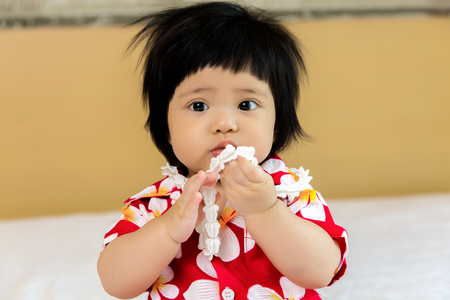 drench: Adorable Asian child girl wearing flower shirt to celebrate Thai new year, Songkran or water festival Stock Photo