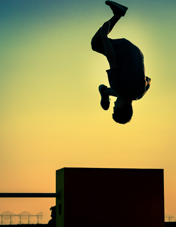 BACKFLIP: A young athlete performing a backflip in front of an obstacle