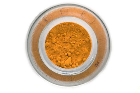 Yellow spice in glass container closeup isolated photo