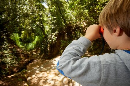 blonde boy watching with the binoculars in the woods forest green