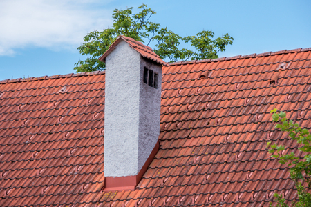 Old style concrete chimney at red clay bricks roof. Foto de archivo