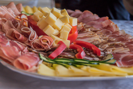 Cold cuts plate with cheese, paprika, prosciutto and smoked ham closeup